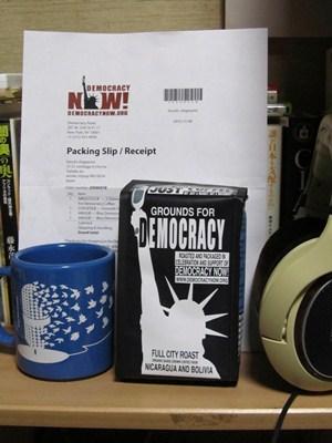 デモクラシーナウ マグカップとコーヒー