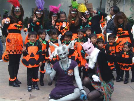 高いレベルのメイク姿で登場した仮装パレード参加者と仮装する子供達