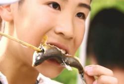 焼き魚を頬ばる子供
