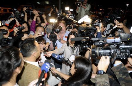 劉暁波氏のノーベル平和賞受賞が決まり、同氏の友人の周りに集まる報道陣=8日