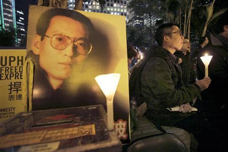 劉暁波氏のポスターのそばで、ろうそくを持って民主化を求める人々=1月、香港