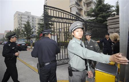 ノーベル平和賞受賞が決まった劉暁波氏の妻、劉霞さん宅に通じる門を閉める警察官ら=8日、北京市内
