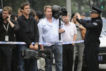 ノーベル平和賞受賞が決まった劉暁波氏の妻を取材するために集まった報道陣を撮影する警察官(右端)=8日、北京市内