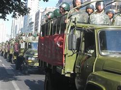 9日、ウルムチ市内を示威行進する、武装警察隊員を満載したトラック(野口東秀撮影)