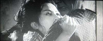 恐ろしい女の顔とかんざし、ひっしで抵抗する保本の表情のアップショット。