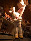 閉店後の薄暗い店内で60球状ボディの腕につかまり考え事をするウサギ。