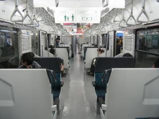 先頭車の車内。E217系と同じセミクロスシートだが、車体幅が小さいため通路もやや狭くなっている。2009年11月28日、千葉駅で撮影。