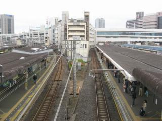 西口の跨線橋から千葉駅構内を見る。中央が「ペリエ1」の建物で、その両脇の線路には木材が敷かれている。