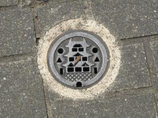 路上に点々と設置されている排水口(?)。姫路城の大天守が描かれている。