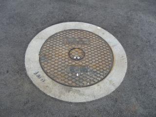 稲毛海浜公園脇の道路上にNAA(成田国際空港)のロゴ入りマンホールが…
