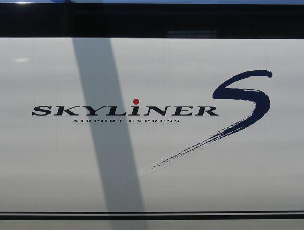 """ボディー側面のロゴ。スピード感あふれる筆書きの""""S""""の文字が大きく描かれている。SKYLiNERの""""i""""の赤丸は日の丸をイメージしている。新鎌ヶ谷駅にて。"""
