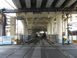 駅の横浜方にある踏切から駅構内を見る。右へ分岐する線路が空港線ホームへ通じる。この平面交差もまもなく解消される。