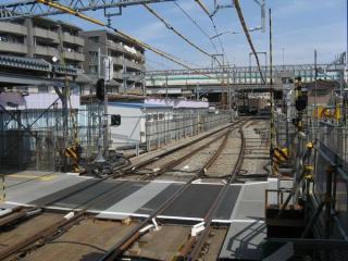 小島新田駅方面を見る。奥の高架橋が首都高速1号横羽線で、その下が産業道路と交差する踏切。