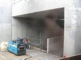 壁面が透明になっている部分から工事中の本設通路を見る。コンクリートの仕切りはエスカレータ用?