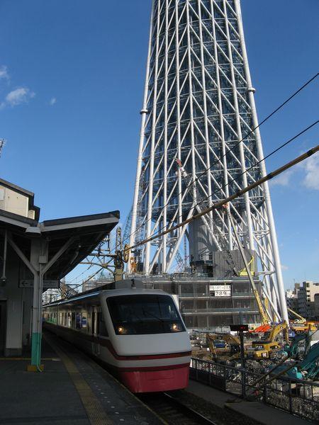 脇で東京スカイツリーの建設が進む業平橋駅と通過する200系特急「りょうもう」
