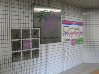 1号出入口階段の踊り場にある野田藤と福島区の史跡のプレート
