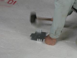 敷き詰めた発泡スチロールに固定用の金具を打ち込む。