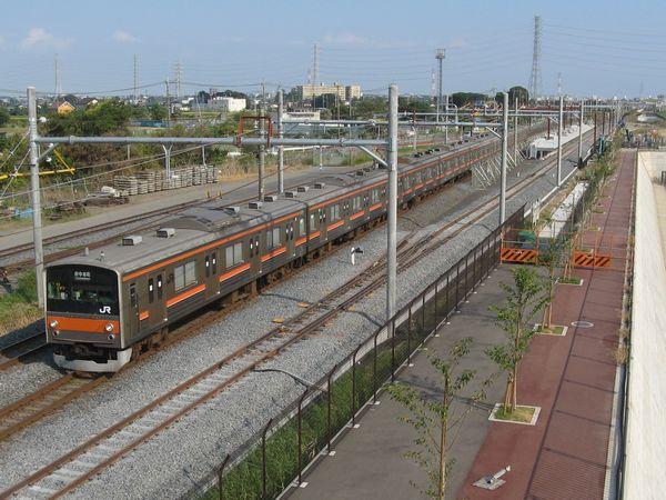 工事中のホーム脇を通過する武蔵野線上り列車。手前のバラストが白い線路が新上り本線。