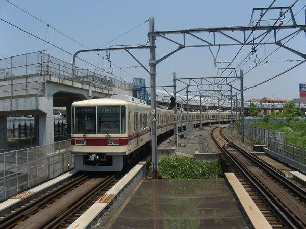 新鎌ヶ谷駅付近で建設中の高架橋と地上線を行く8800形電車。